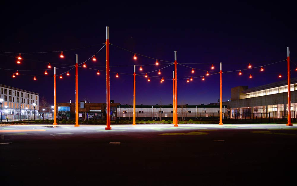 The catenary lighting installation at the D Street Corridor in Boston, Massachusetts, helps draw attention to the pedestrian connection between the Boston Convention and Exhibition Center (BCEC) and the surrounding neighborhood and businesses.