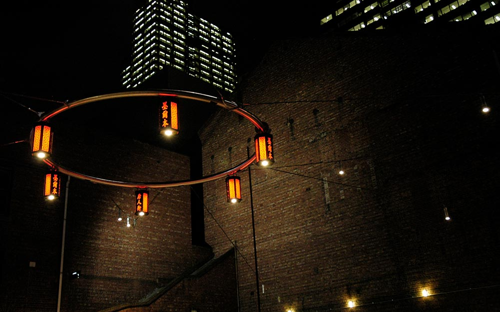 This dimly lit square in Melbourne's China town has been transformed with the installation of a startling and functional catenary lighting system