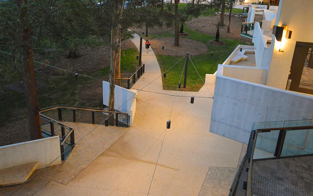 To light the public spaces and walkways, a catenary lighting systems was envisaged to provide warm contrast and directional lighting from a suspended cable net