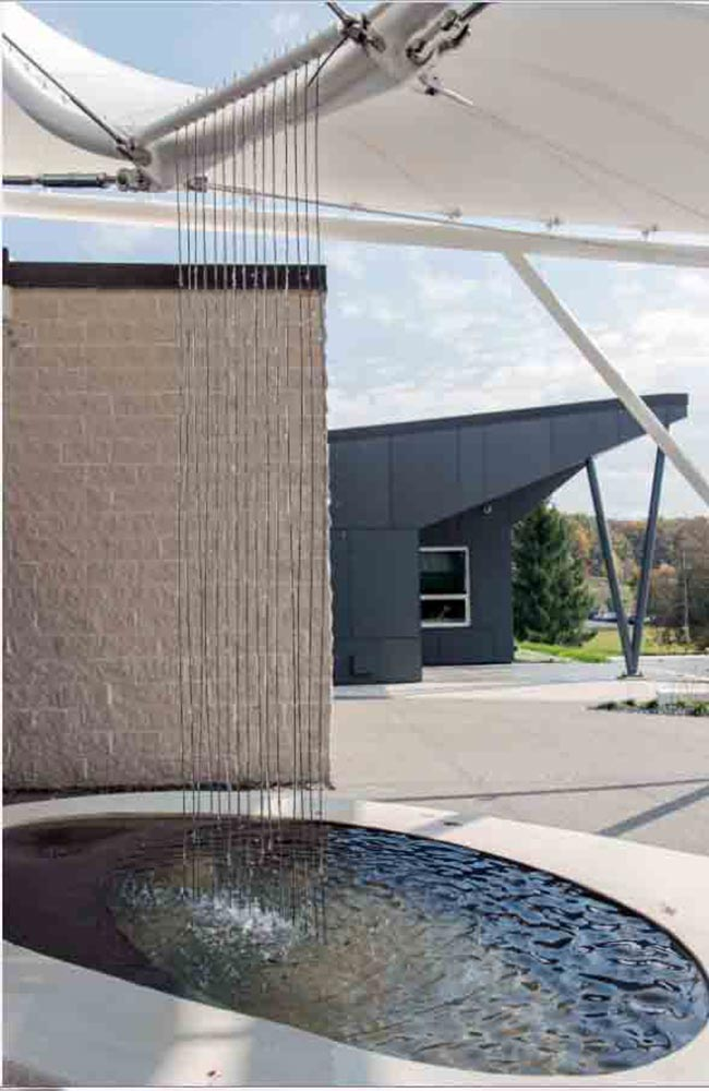 Seaman Corporation is known for their role as a world leader in providing innovative solutions for tomorrow's high performance industrial fabric needs. Given this, it is fitting that their Wooster, Ohio headquarters main entrance is marked by an installation of striking fabric pavilion structures, which incorporate their own fabric material.