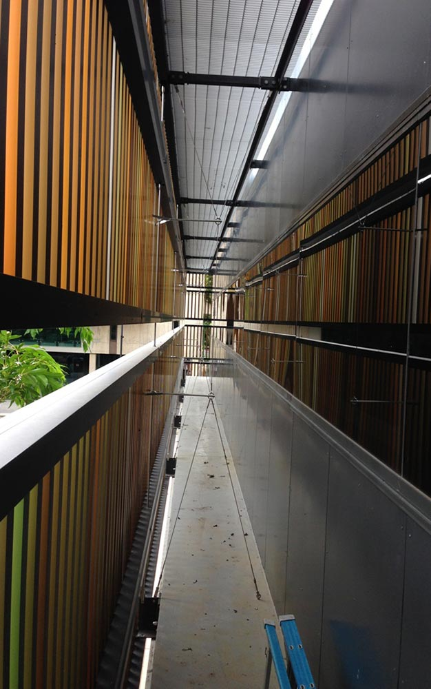 Ronstan Tensile Architecture engineered an ARS3 rod support structure with custom cable braces to carry the coloured aluminium battens of the UQ Michie Building