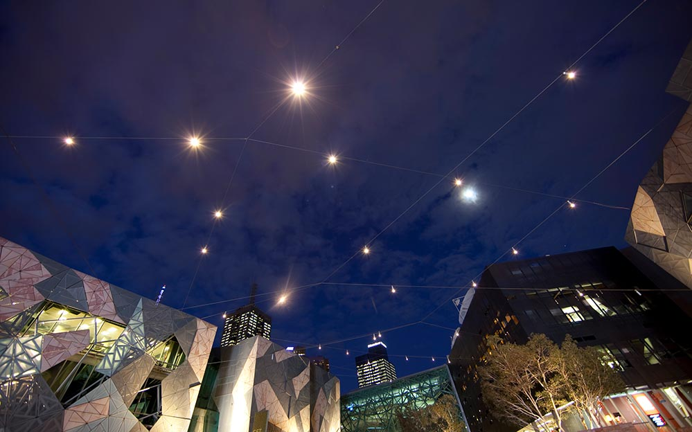 The catenary lighting system pinpoints landscape features and the system creates a unique and inviting ambience to Melbourne's famous Federation Square