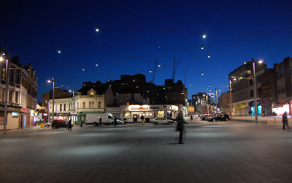 The catenary lighting at Beresford Square in Woolwich ensures a unique ambience with a clear and useable footprint without intrusive support structures.
